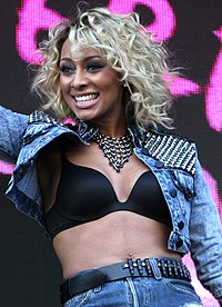 A blonde woman with dark skin, wearing a blue jean jacket and blue short jeans.