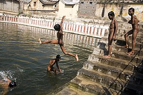 Boys skinny dipping in a sacred tank of water in India