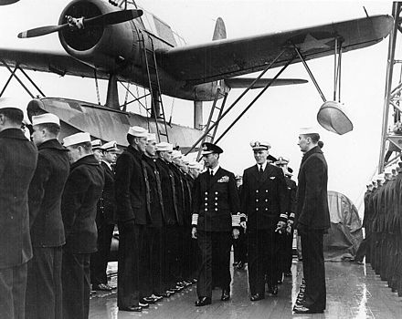 Midshot with a large single engined propeller warplane in background. A man with military ribbons covering his chest—the King (see caption)—accompanied by navy officers walks down a lines of sailors who stand rigidly at attention.