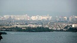 Un lac à l'avant-plan, puis une ville basse, des gratte-ciels plus loin et au fond des montagnes.