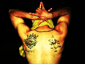 Gang - Latin King gang member showing his gang tattoo, a lion with a crown, and signifying the 5 point star with his hands