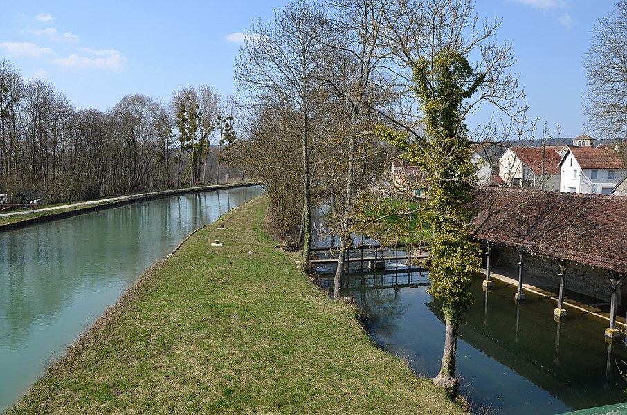 Commune of Tanlay, Yonne, Bourgogne, France. Canal of Burgundy on the left, on the right the channel coming from the castle of Tanlay, here at the wash-house in Commissey. The Armançon river is on the left behind the road that closely follows the canal - we can see a lorry passing by on that road, grey trailer and white tractor. View from the bridge over the Armançon river, the canal and the channel.
