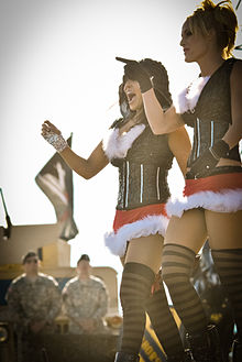 Two Caucasian women in matching outfits walk in front of two men in military uniforms. Both wearing black tops and red skirts with thigh-high black stockings, the woman on the left has dark brown hair and her hood up, while the blonde woman on the right is pointing to the left.