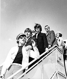photographie en noir et blanc de six personnes en haut d'une passerelle à la sortie d'un avion de la compagnie Iberia.