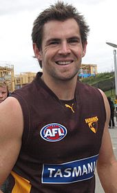 A male athlete with dark hair wearing a sleeved jersey smiles at camera.