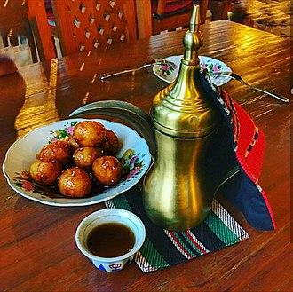 Emirati cuisine - Luqaimat (Called Lugaimat in Emirati Dialect) served with Arabic coffee. Luqaimat is a famous traditional Emirati dessert.
