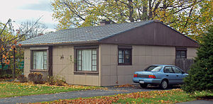A brown house with the same grid-pattern siding and a blue car parked in a driveway on the left.