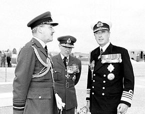 Three men in dark military uniforms with peaked caps