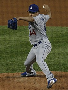 A man wearing a gray baseball uniform and blue baseball cap throws a baseball with his right hand.