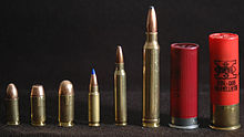 Photo of various cartridges, showing from left to right: 9×19mm Parabellum, .40 S&W, .45 ACP, 5.7×28mm, 5.56×45mm NATO, .300 Winchester Magnum, 2.75-inch 12 gauge, and 3-inch 12 gauge