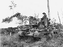 Black and white photo of a tank with flames coming out of the gun barrel on its turret. Two men wearing military uniforms are leaning on the side of the tank.