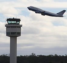 A plane taking off, with a control tower in the foreground