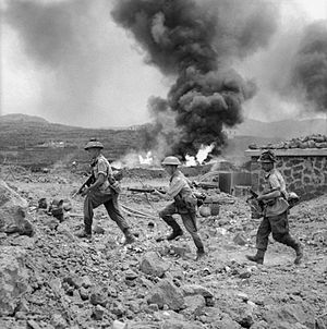 Operation Corkscrew - Image: Men of 1st Battalion advance past a burning fuel store on Pantelleria