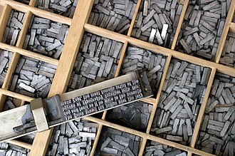 Typography - Movable type being assembled on a composing stick using pieces that are stored in the type case shown below it