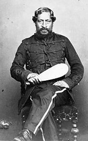 Formal seated portrait photograph of a man in his 50s wearing a uniform and holding a patu.