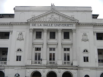 De La Salle University - The facade of DLSU looms over Taft avenue and features the statue of St. La Salle atop a cornice gable straddling Greek style columns.