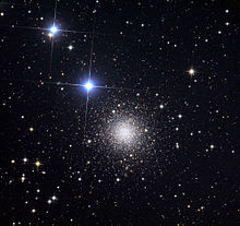 a round cluster of tiny distant stars with two bright bluish stars to the upper left