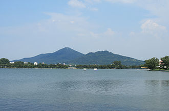 "Purple Mountain or Zijin Shan, located to the east of the walled city of Nanjing, is the origin of the nickname ""Jinling"". The water in the front is Xuanwu Lake Nanjing XuanWuLake Purple and Mountain.jpg"
