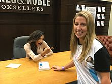 A young dark-haired woman sits at a desk in a bookstore, pointing to a blonde woman wearing her likeness on a t-shirt.