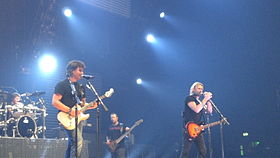 A color photo of four band members on stage, in the foreground the audience can be seen.
