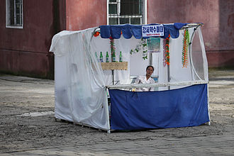 A North Korean vendor on a makeshift market stand selling goods.