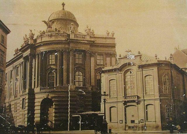 Старое здание Бургтеатра (справа), где шли премьеры всех опер Моцарта. Здание было снесено в 1888 году. Слева— Михайловское крыло Хофбурга.