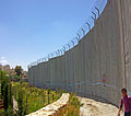 Palestinian boy with Israeli separation barrier at Bethlehem.jpg