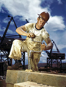 An American carpenter wearing overalls, boots, and a hard hat bores a hole with a hand drill.