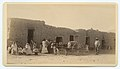 People and cart in front of adobe houses (8244805733).jpg