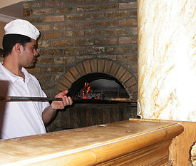 man using an oven of a pizzeria.