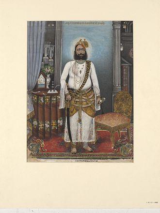 Alwar State - Portrait of Thakur Raja Bakhtawar Singh, standing in a European-style interior.