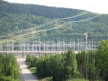Power lines reach a hub in a densely forested area. A road going downhill leads to a forest of metal pylons.