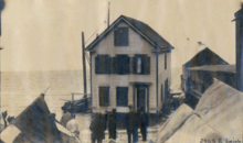 old photo showing a house being floated on small barges in the harbor