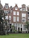 foto van Huis met puntgevel waarin goede roedenverdeling, bovenlicht en gevelsteen waarop st