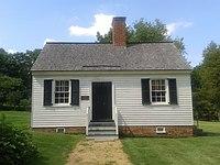Malá chata s bílými stěnami, černými dveřmi a cihlovým komínem