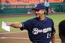 "A man in a navy baseball uniform with ""Brewers"" across the chest and a navy cap with an ""M"" on the center"