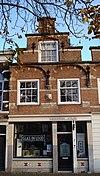 foto van Pand met trapgevel, in Zuidhollandse trant, met uitgekraagde ontlastingsbogen op kraagstenen, natuurstenen banden en sierankers