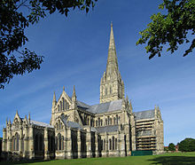 A longshot of Salibury Cathedral shows the building rising from a green lawn, with its tall grey masonry spire against the blue sky. The exterior shows the same harmony in the groupings of simple windows that is apparent in the interior view.