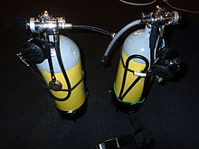 A pair of cylinders showing the regulators set up for sidemount diving. Each regulator has a short low-pressure inflator hose projecting towards where the diver's body would be, and the DV hoses are stowed under bungees. The submersible pressure gauges are on short hoses aligned with the cylinder axes.