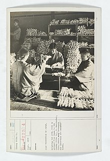 Four men weigh bundles of raw silk in Japan, in September 1918.