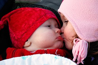 Affection - A young girl kisses a baby on the cheek.