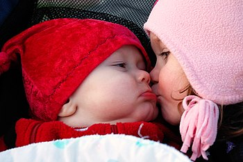 English: A young girl kisses a baby on the cheek.