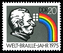 "The horizontal format stamp shows the head of Braille in profile from the right side as a black and white bas-relief on the left half against a gray background.  The facial features are strongly modeled and appear very three-dimensional, the eyes are closed.  To the right of his forehead, roughly in the upper center of the stamp, the six Braille dots are arranged as white circular disks.  A rainbow seems to spring from them, leading first to the right and then in an arc to the lower right corner of the stamp.  At the top right in the free space above the rainbow, the letters ""DDR"" and the number ""20"" are in black, at the bottom of the stamp, under the gray main motif, ""WELT-BRAILLE-YEAR 1975"" is written in black and white."
