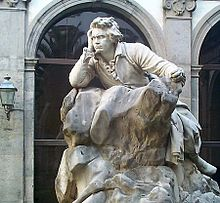 Statuon de viro sidanta en roko, kun intensa rigardo.
