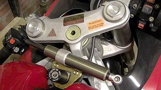 Steering damper - Transverse linear motorcycle steering damper (centre foreground)