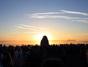 The sun behind the Heel Stone at Stonehenge, s...
