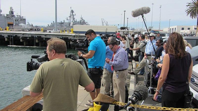 Television broadcast crews line up awaiting arrival of USS Vandegrift crew.jpg