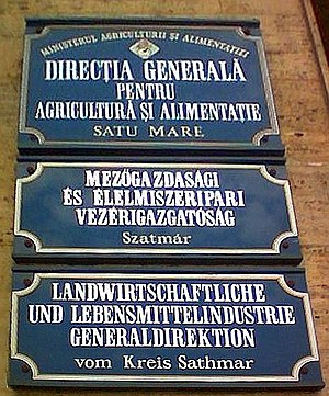 "Agglutination - The middle sign is in Hungarian, which agglutinates extensively. (The top and bottom signs are in Romanian and German, respectively, both inflecting languages.) The English translation is ""Ministry of Food and Agriculture: Satu Mare County Directorate General of Food and Agriculture""."