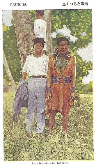Chuuk Lagoon - At right, a traditionally dressed older Truk man. Dress includes earrings, belt, sleeveless textile pullover, bracelets. Circa 1930s.