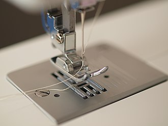 Presser foot raised with feed dogs visible Two threads threaded sewing machine.jpg